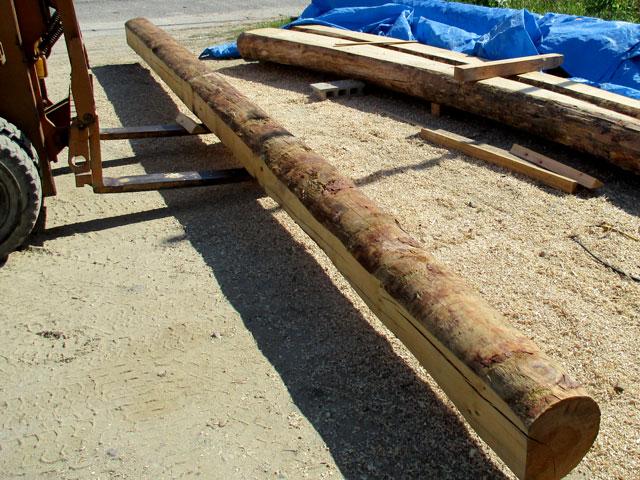 屋根裏に使う梁丸太の皮を剥く